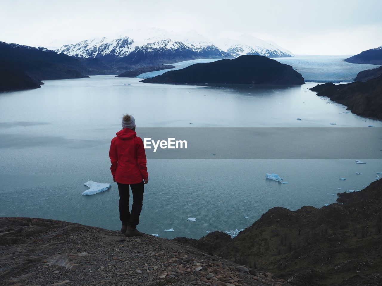 Rear View Of Woman Standing On Mountain Against Sea During Winter