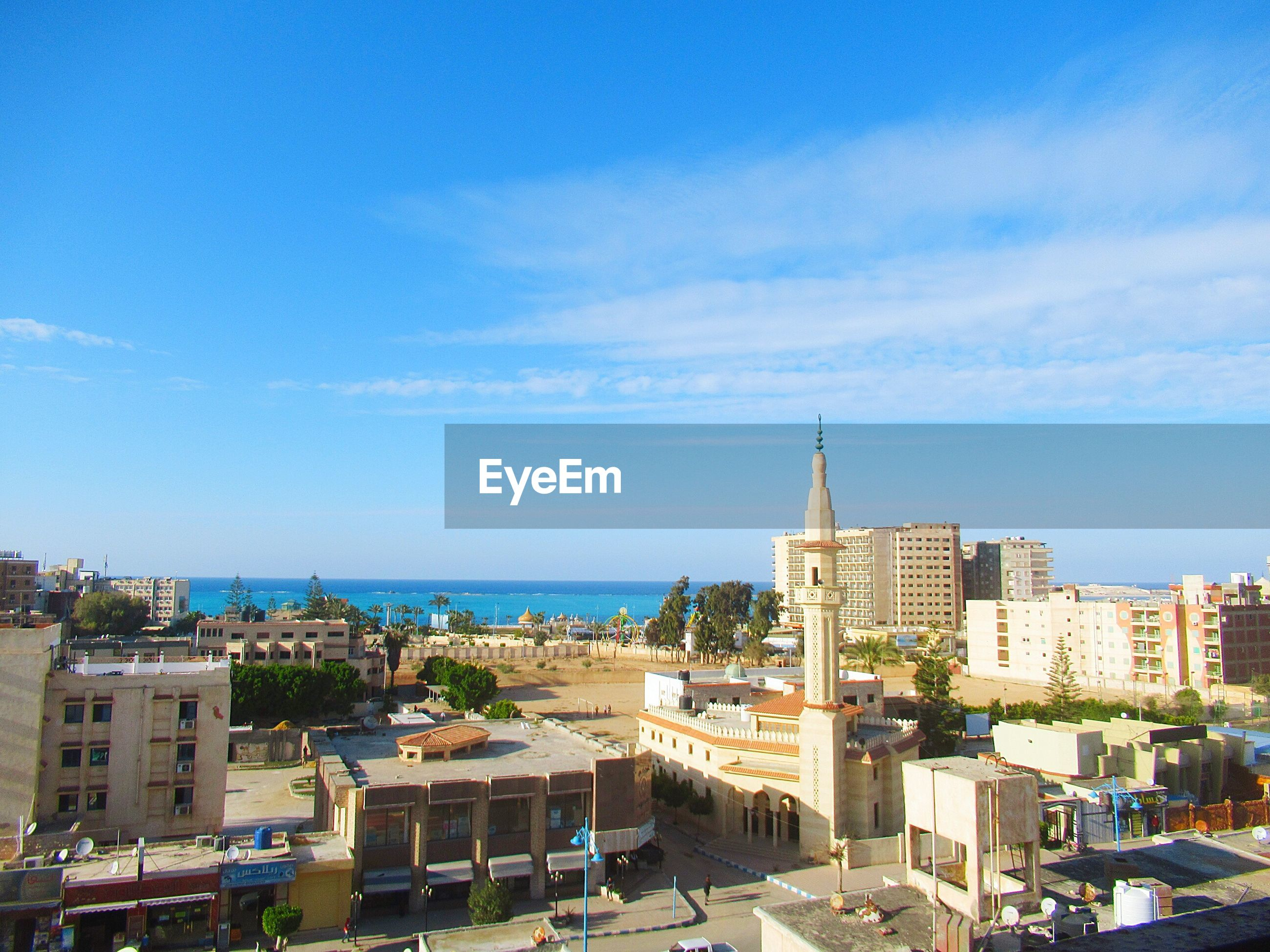 High angle view of buildings and sea against blue sky