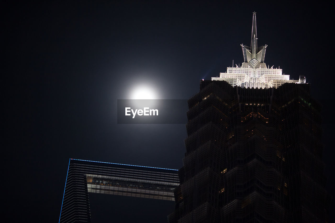 Low Angle View Of Moon Shining Over Illuminated World Financial Center At Night