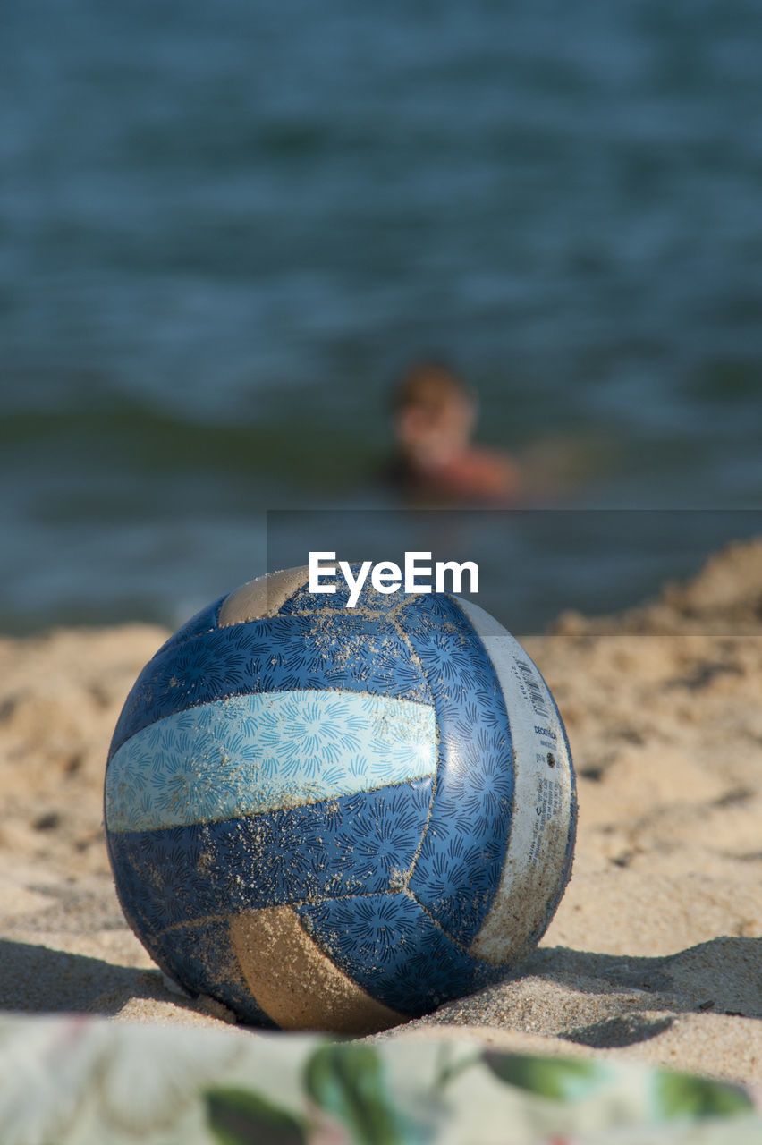 beach, land, focus on foreground, day, nature, water, sunlight, close-up, ball, sphere, outdoors, selective focus, no people, sea, blue, sand, leisure activity, solid, metal