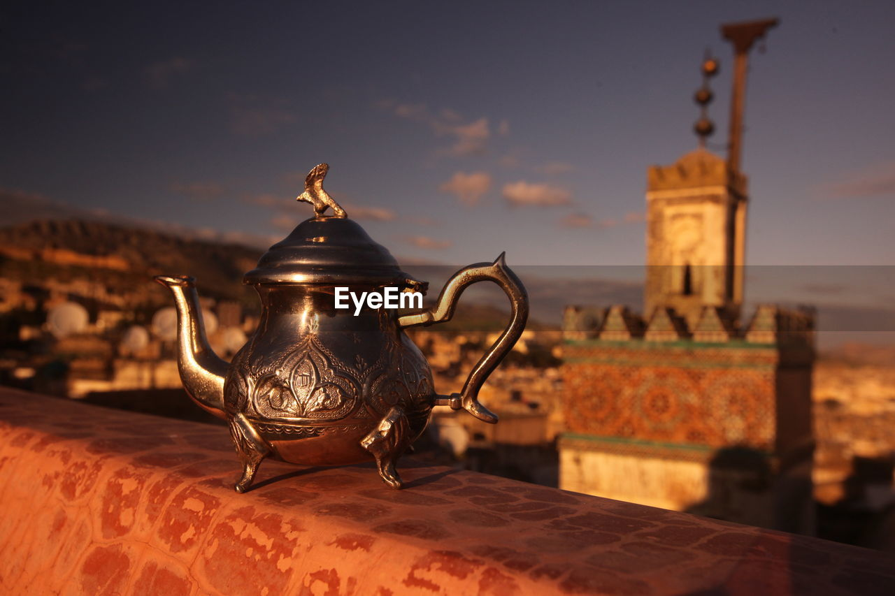 Metallic Teapot On Table Against Town