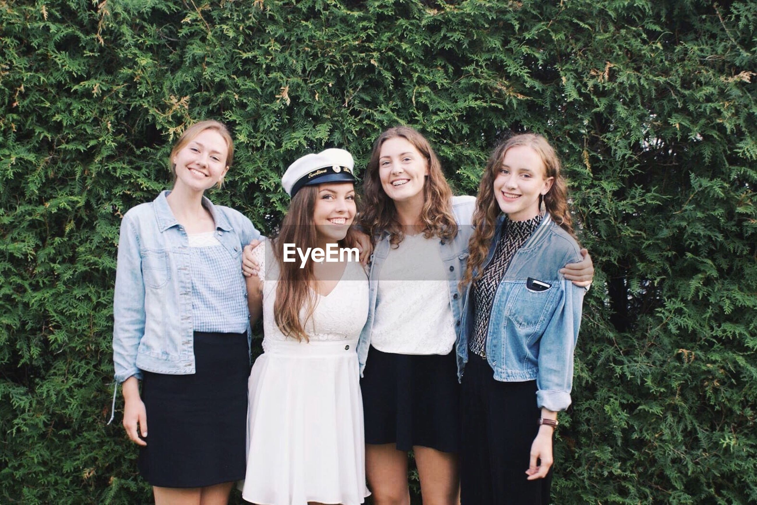 togetherness, casual clothing, three quarter length, looking at camera, young women, front view, portrait, friendship, smiling, day, long hair, outdoors, lifestyles, young adult, grass, leisure activity, standing, real people, hands in pockets, nature, happiness, tree, adult, people, adults only