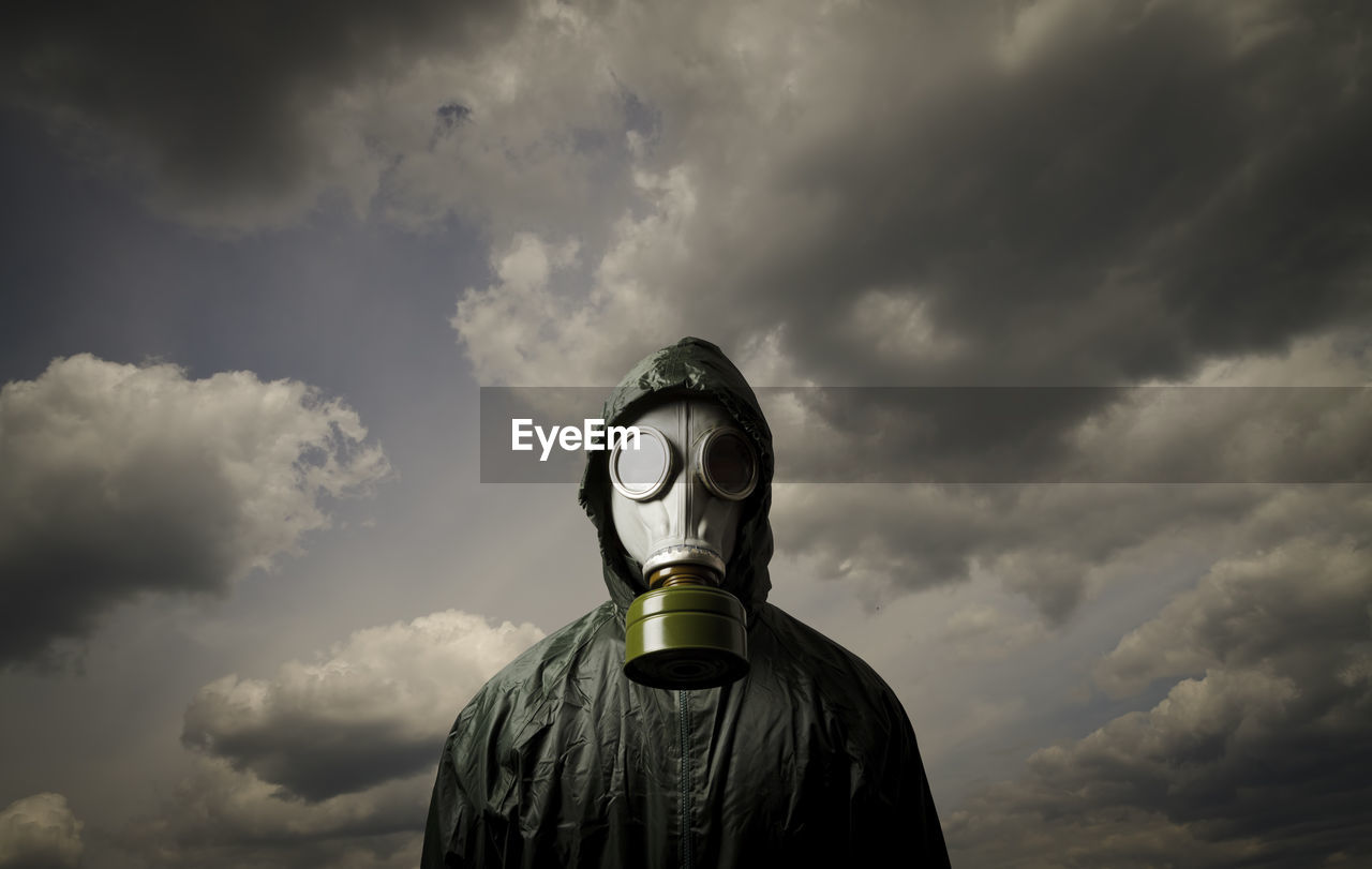 Person wearing gas mask while standing against cloudy sky