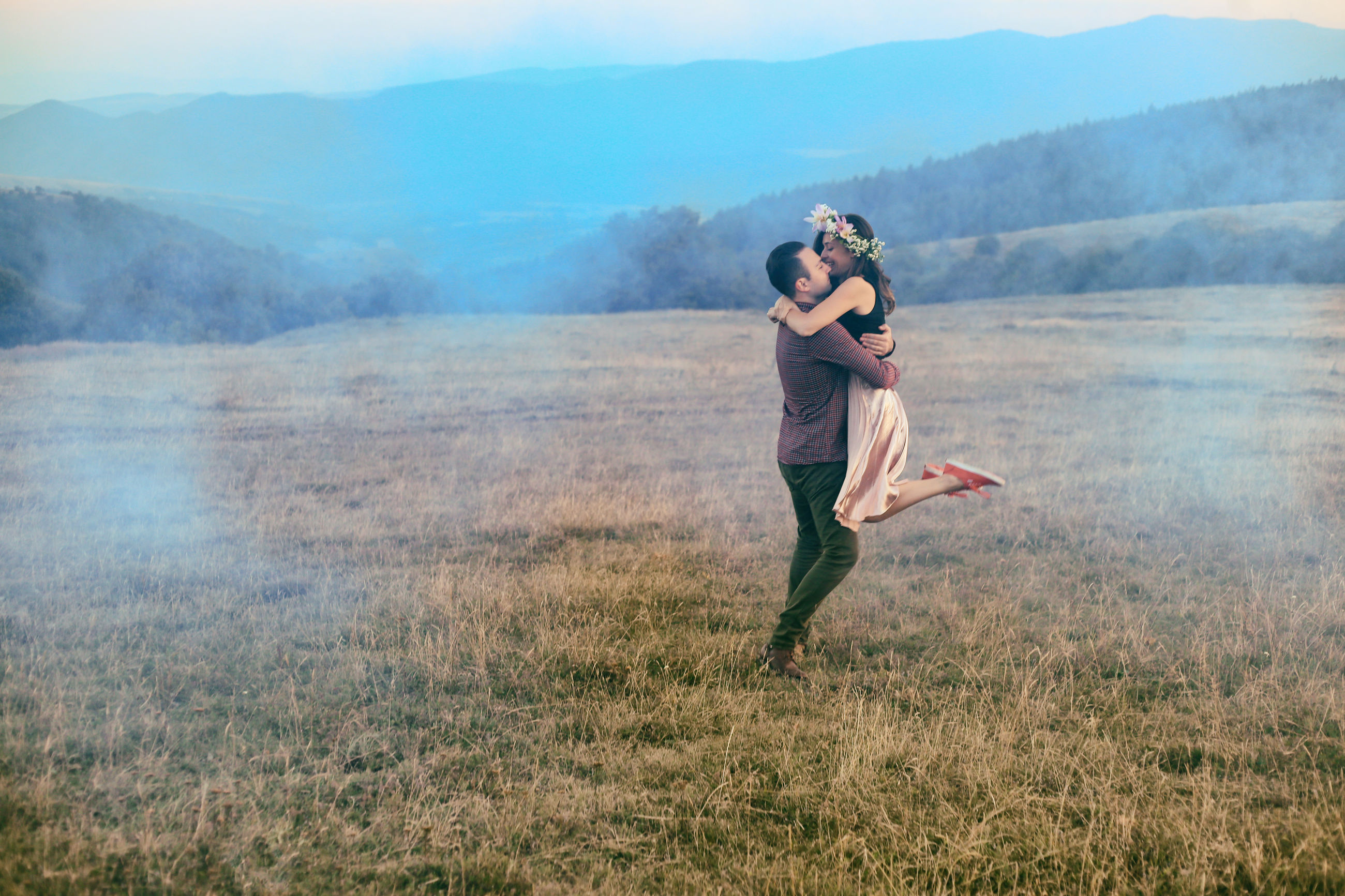 Full length of young couple embracing on field