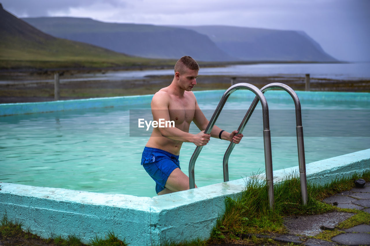 FULL LENGTH OF SHIRTLESS MAN STANDING BY SWIMMING POOL
