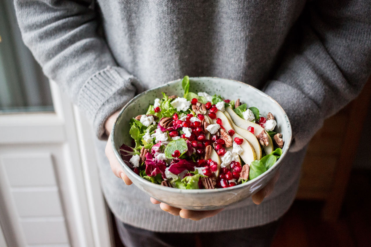 Midsection Of Person Holding Fresh Salad In Bowl