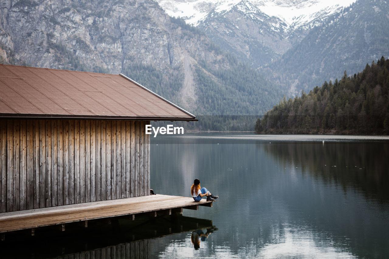 MAN IN LAKE AGAINST MOUNTAIN