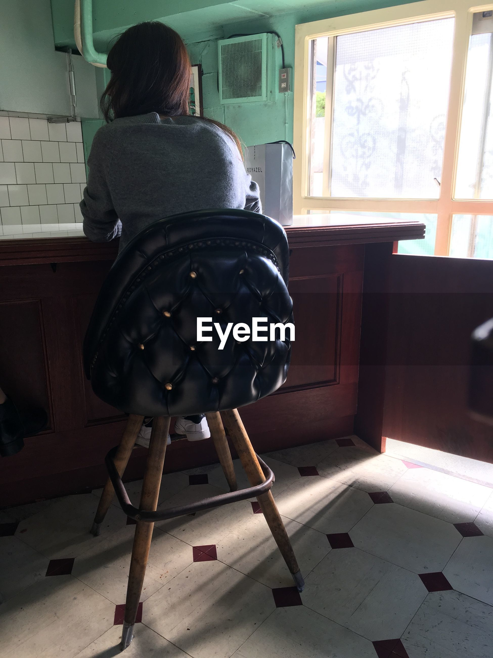 Rear view of woman sitting on chair at home