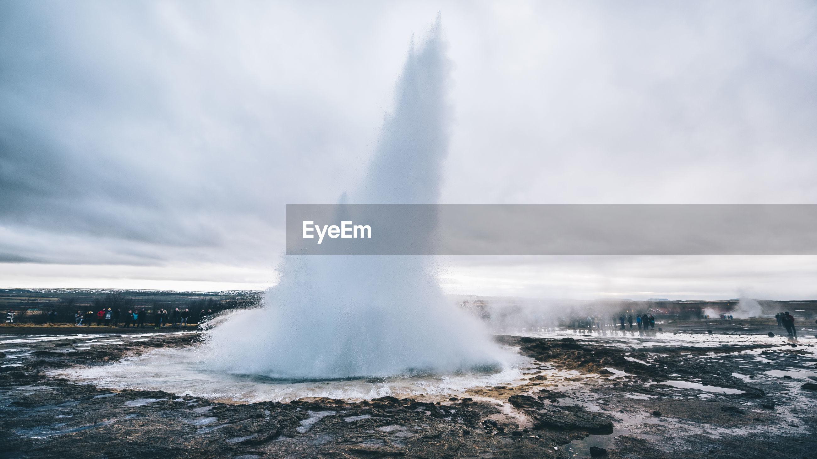 Hot spring erupting against sky