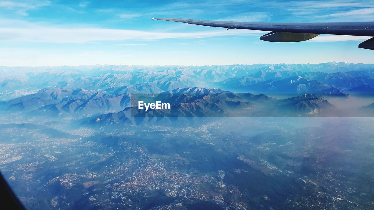 air vehicle, airplane, mode of transportation, transportation, scenics - nature, flying, beauty in nature, aircraft wing, aerial view, landscape, cloud - sky, mountain, sky, travel, mid-air, no people, environment, mountain range, day, nature, outdoors