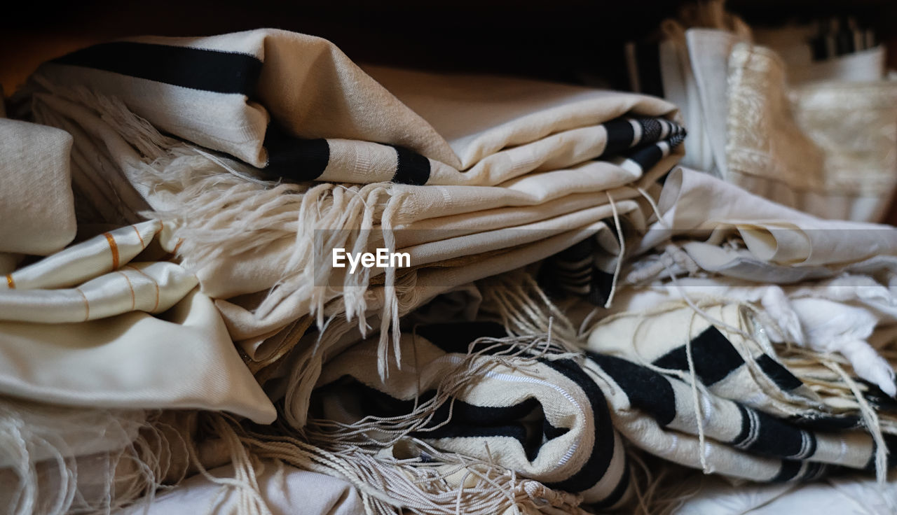 indoors, still life, large group of objects, no people, close-up, textile, high angle view, stack, abundance, choice, messy, white color, variation, bed, crumpled, tied up, furniture, bag, clothing, focus on foreground