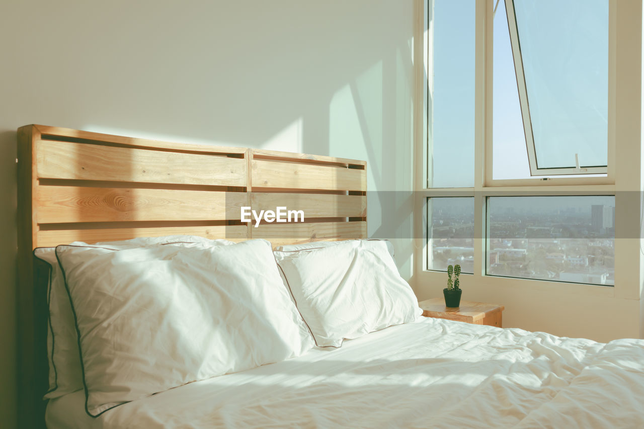 Loft white bedroom with soft sunlight of winter morning.