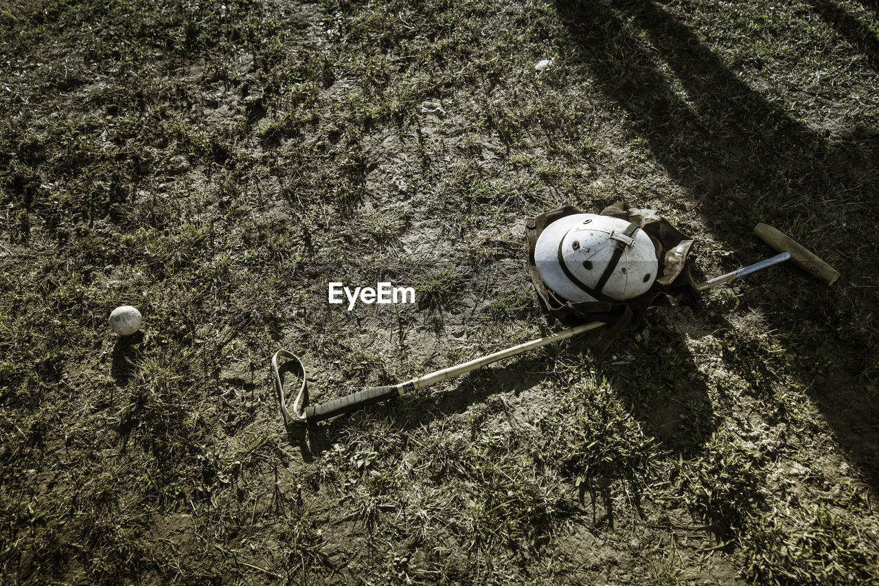 High angle view of helmet with polo mallet and ball on field