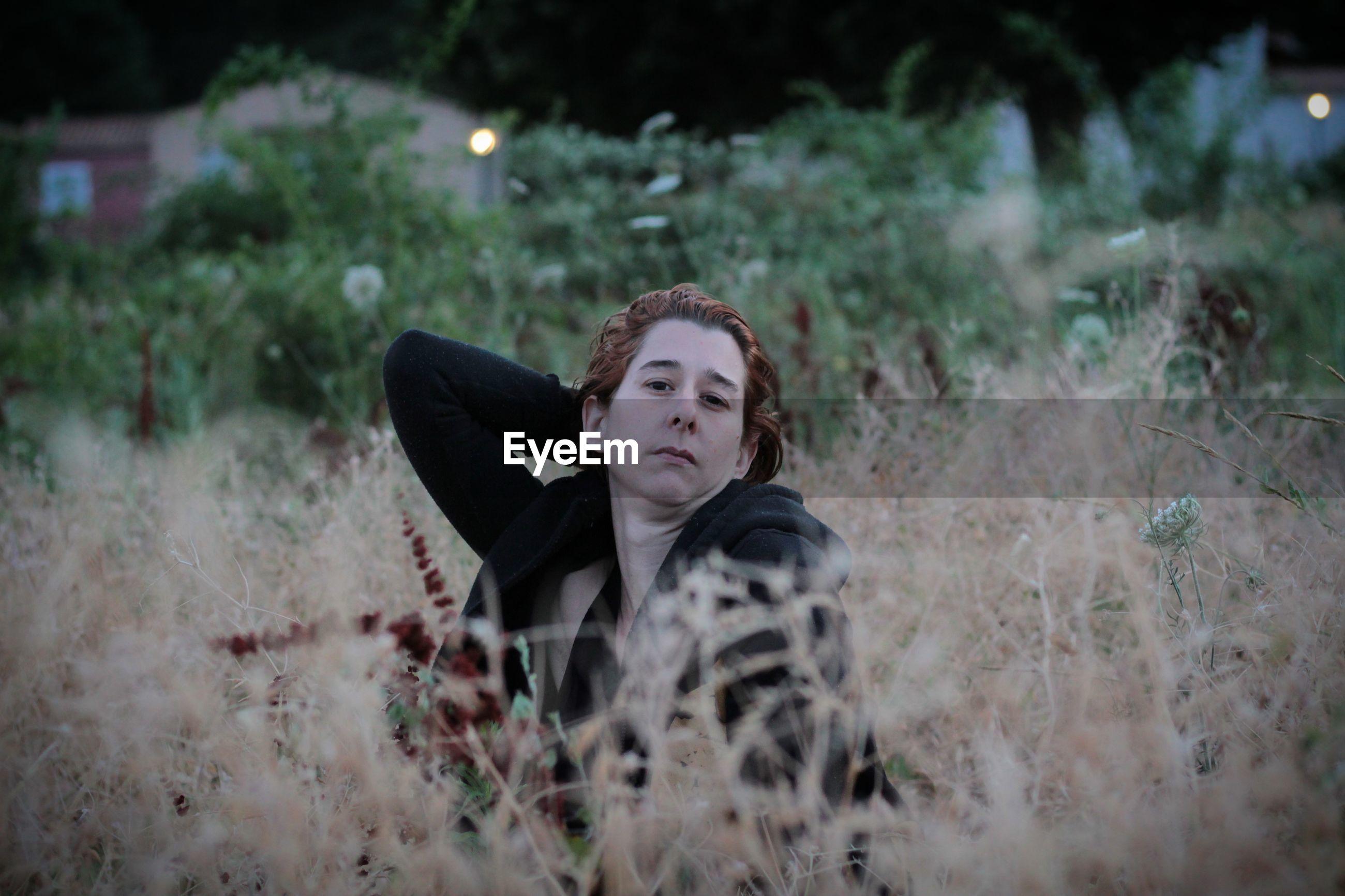 Portrait of woman sitting amidst plants on field