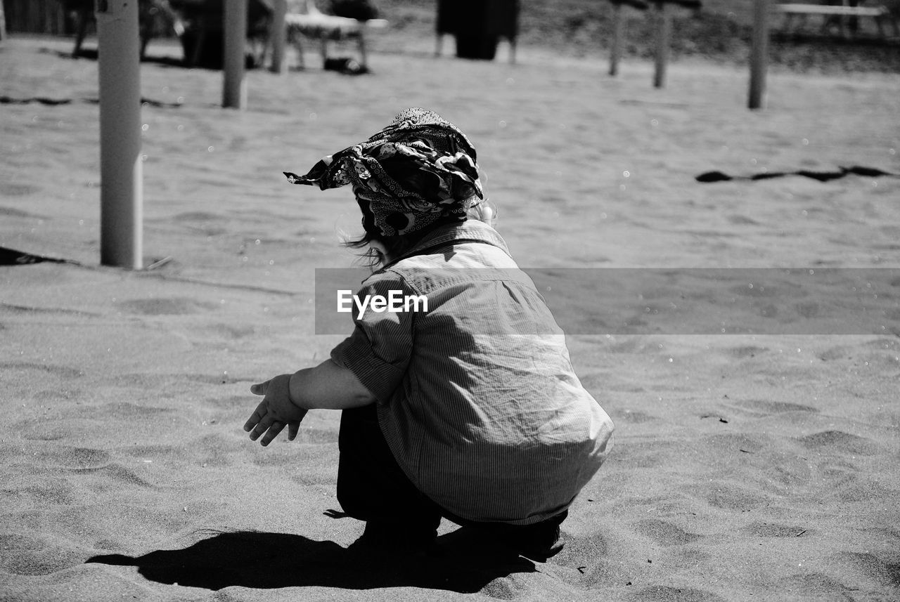 Rear view of baby girl crouching on sand at beach during sunny day