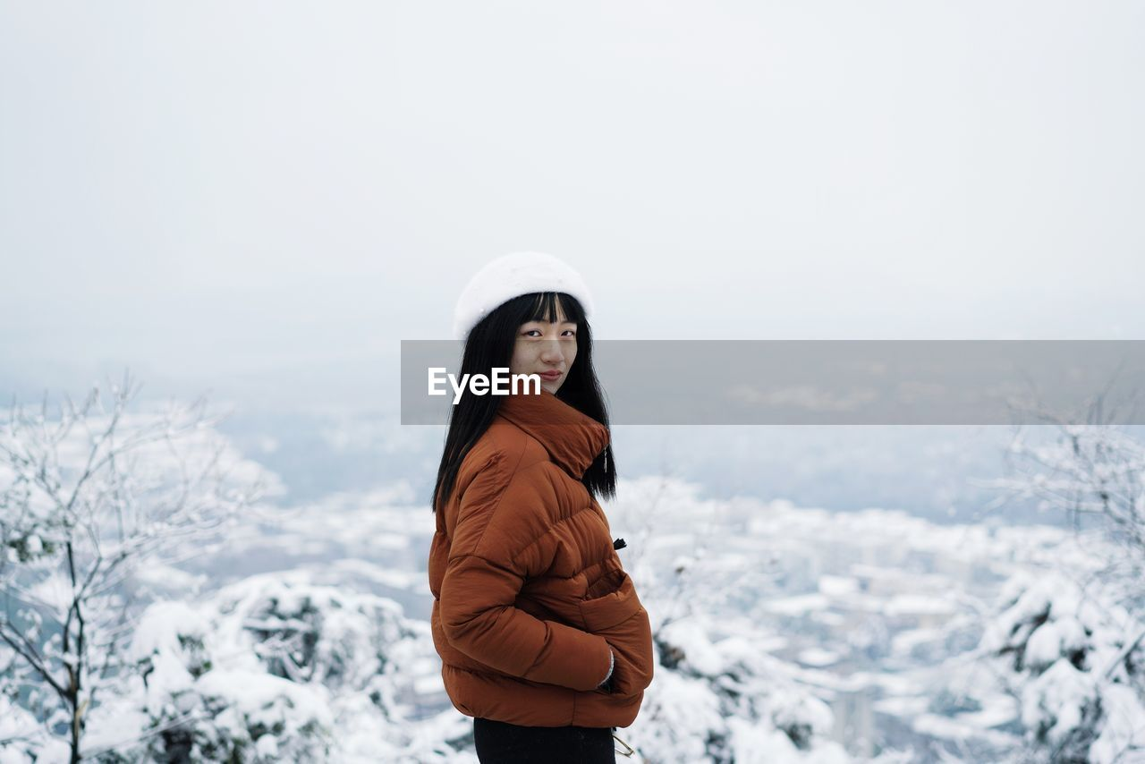 Portrait Of Woman Standing On Snow Against Sky