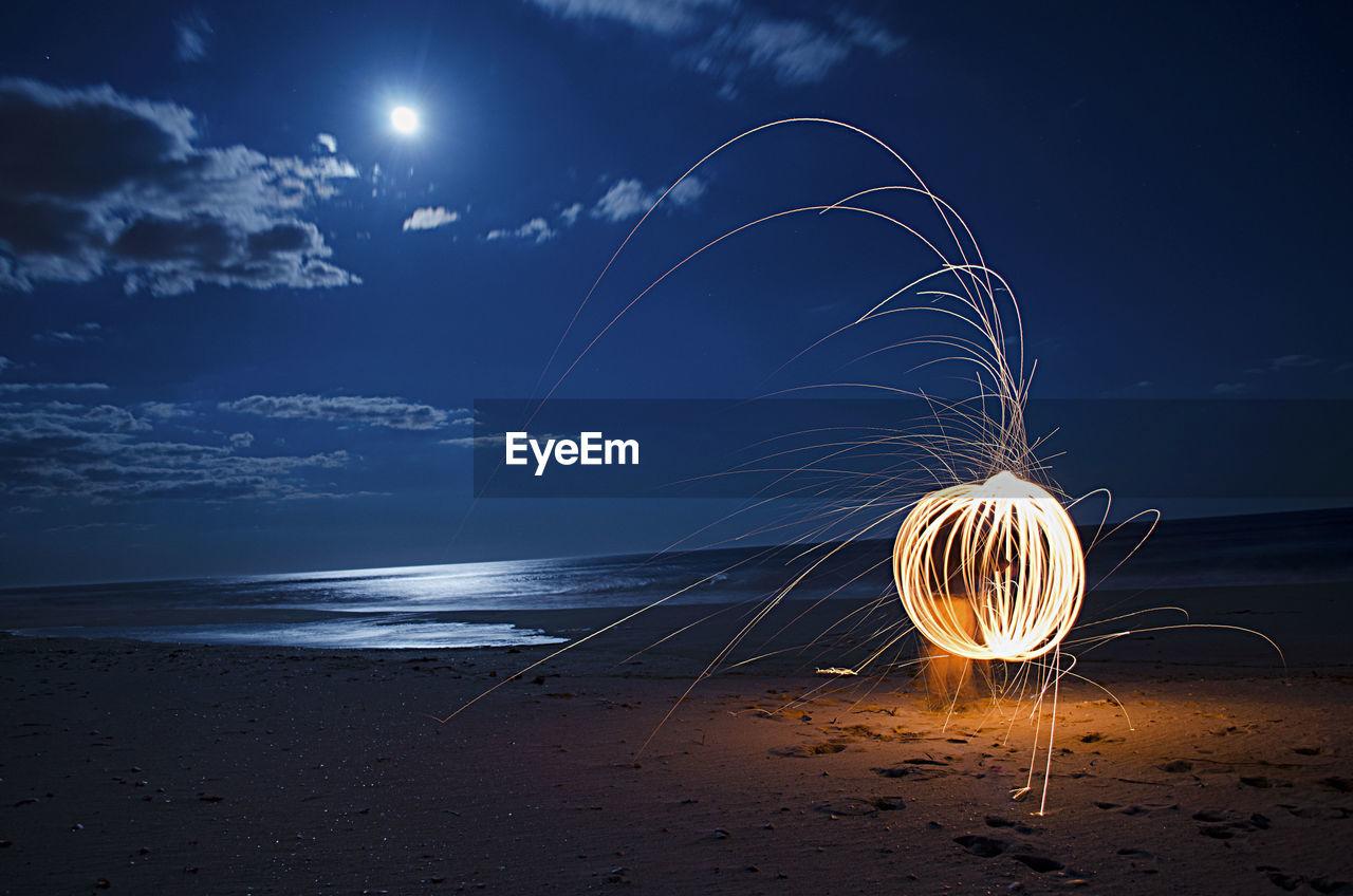 Burning steel wool firework on beach at night