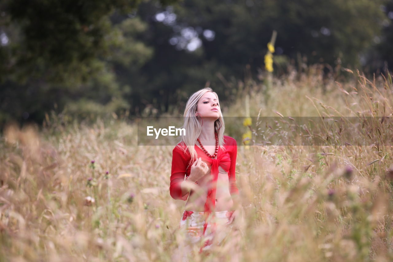young adult, one person, young women, real people, leisure activity, selective focus, red, outdoors, casual clothing, lifestyles, standing, field, nature, plant, beautiful woman, tree, day, growth, blond hair, flower, people