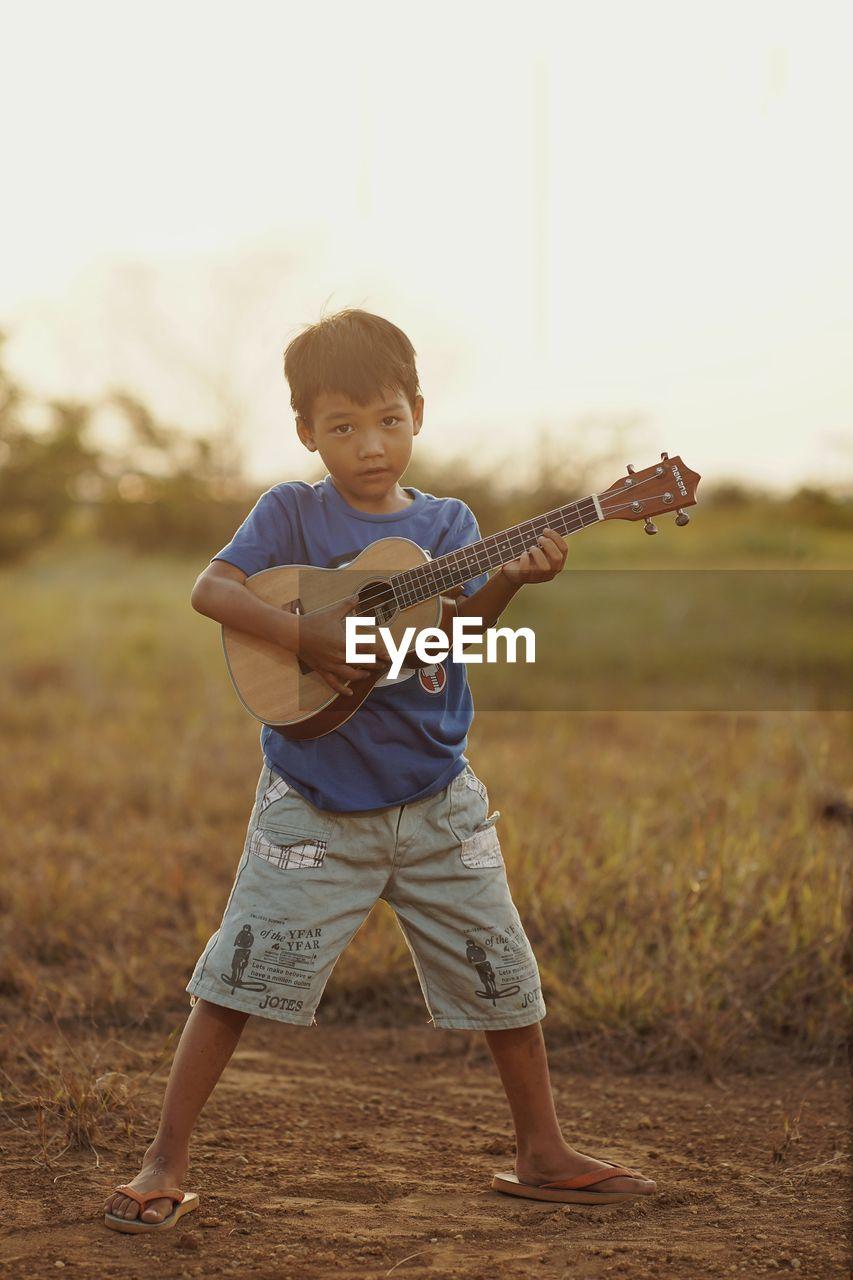 Full length of boy standing on field playing ukulele