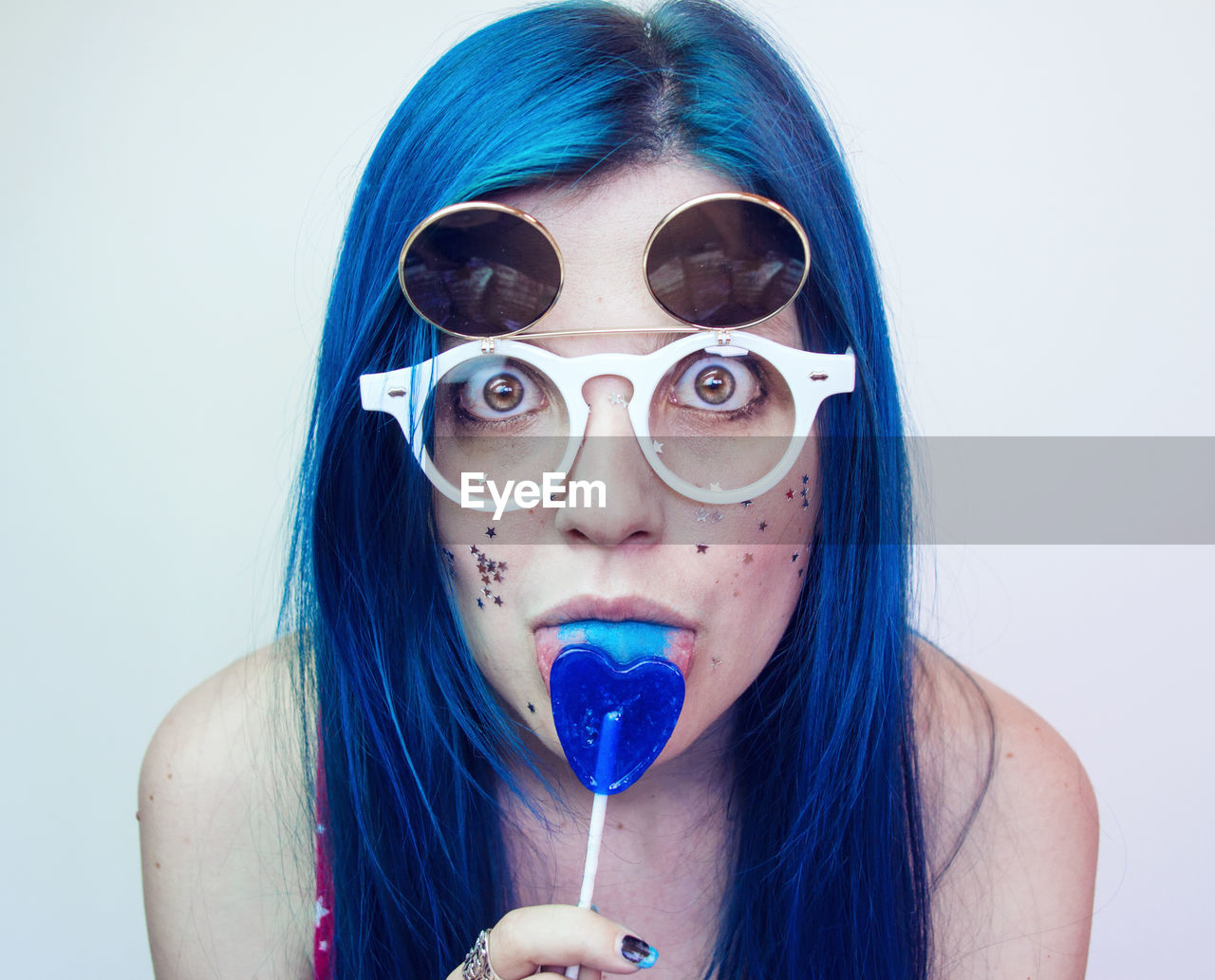 Portrait Of Woman Wearing Sunglasses While Eating Candy Against Wall