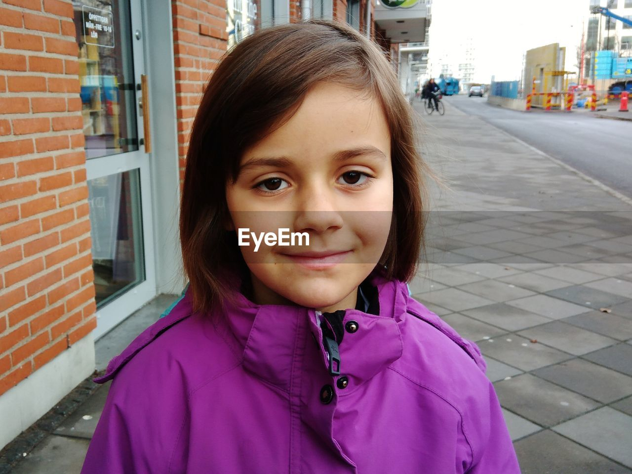 Portrait Of Smiling Girl Standing On Sidewalk