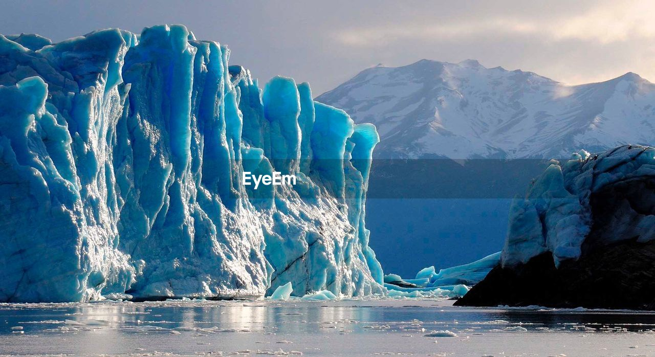 Scenic view of glacier in sea against snowcapped mountains