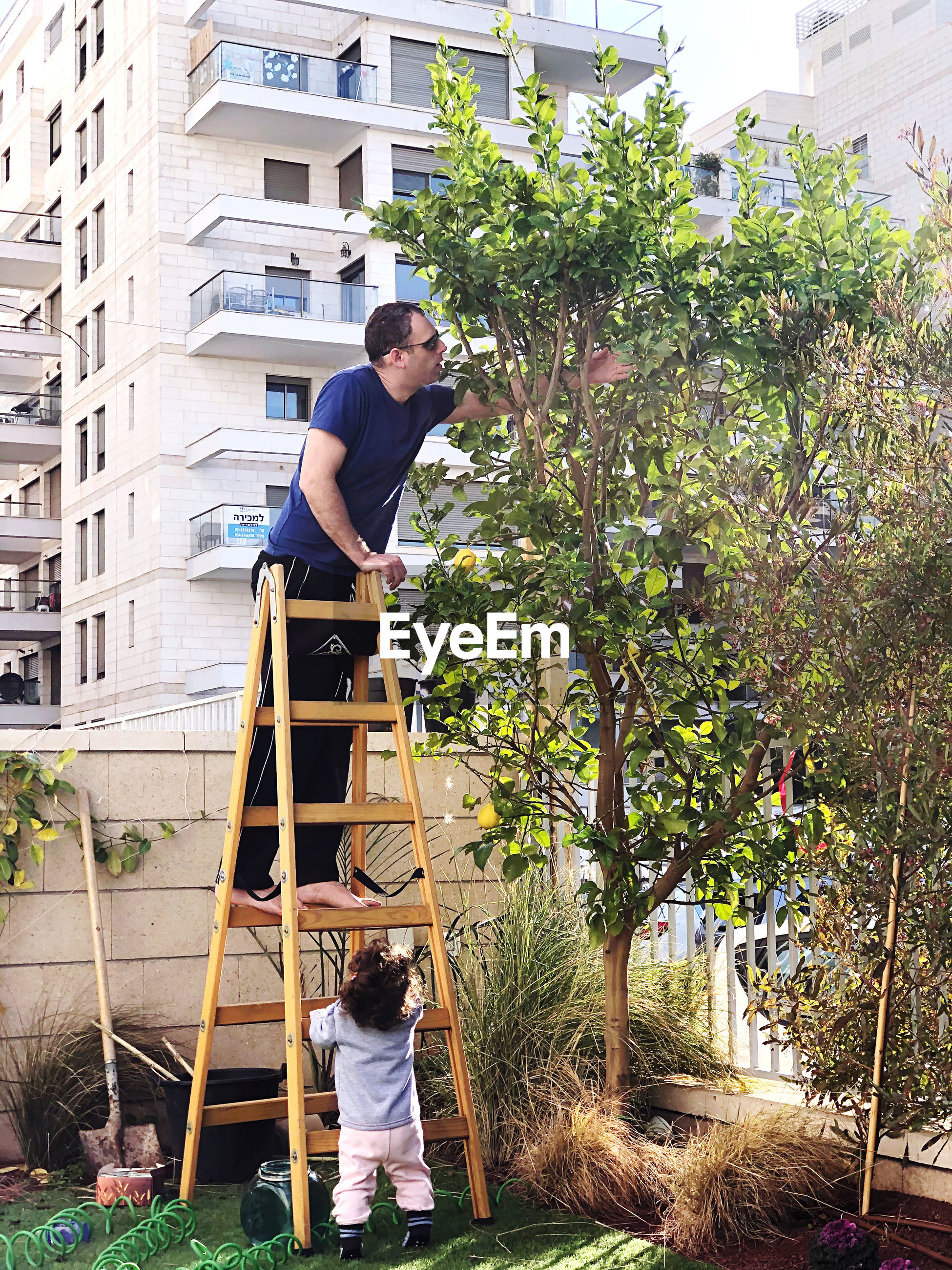 Man standing on a ladder in front of building and a his daughter watching him