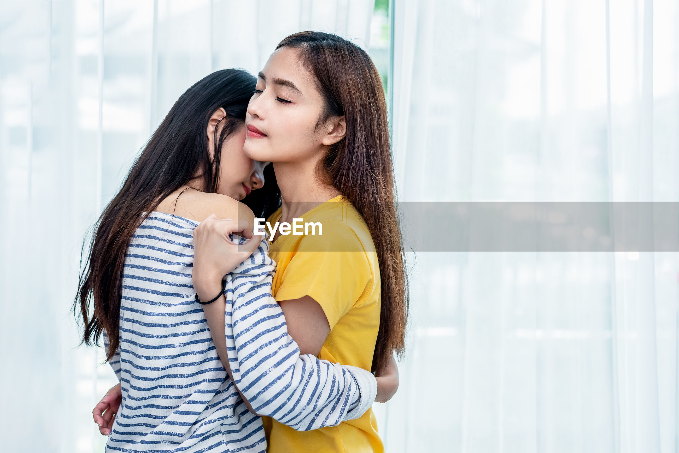 Lesbian couple embracing at home