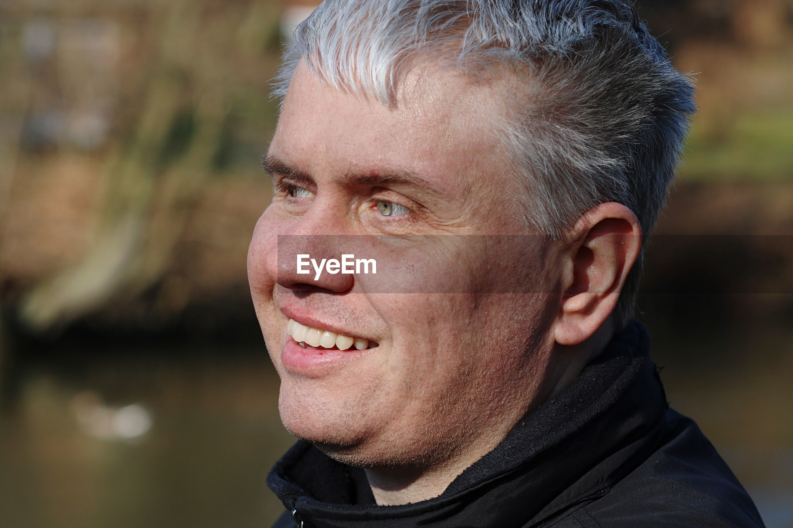 Close-up of smiling man looking away outdoors