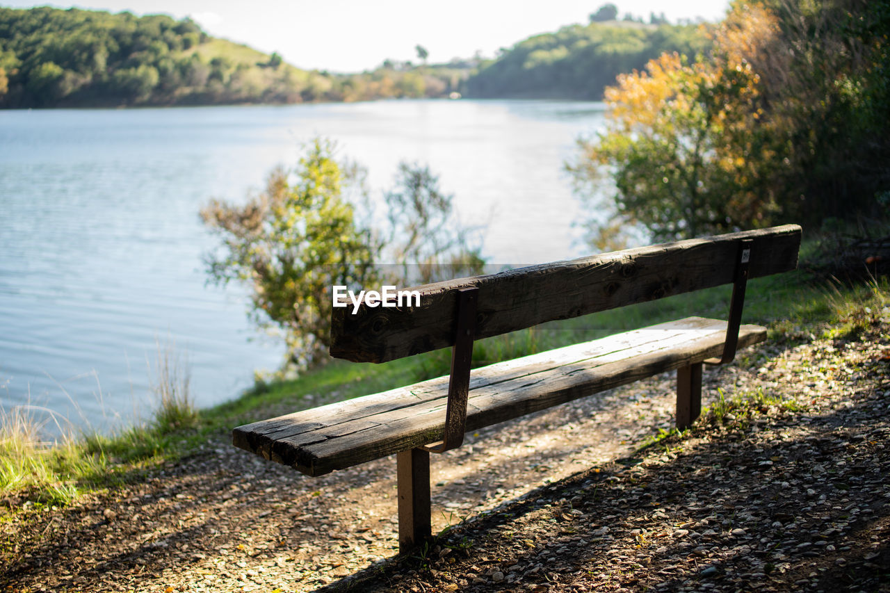 Empty Bench By Lake Against Trees
