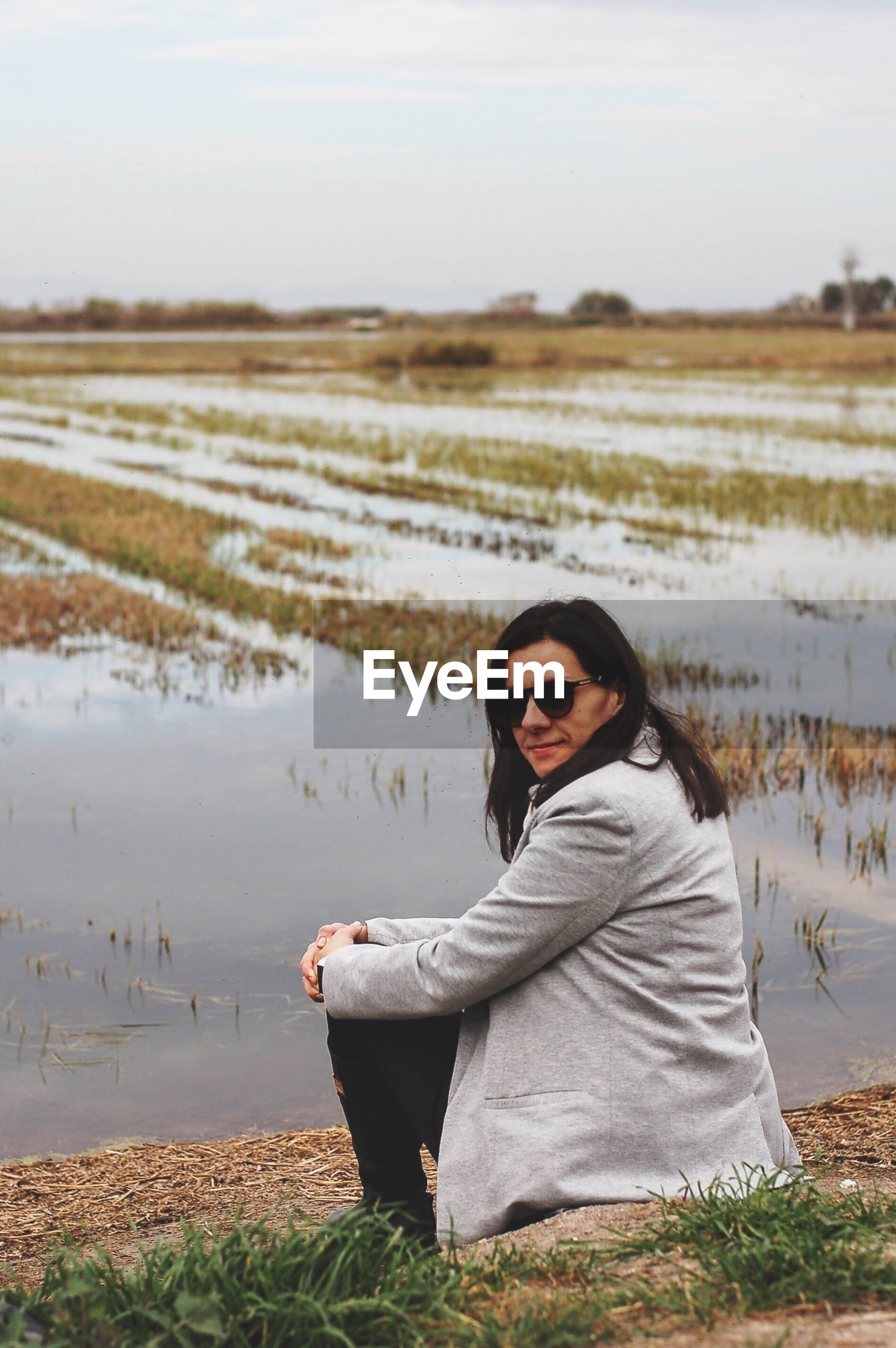 Portrait of woman sitting on field against sky