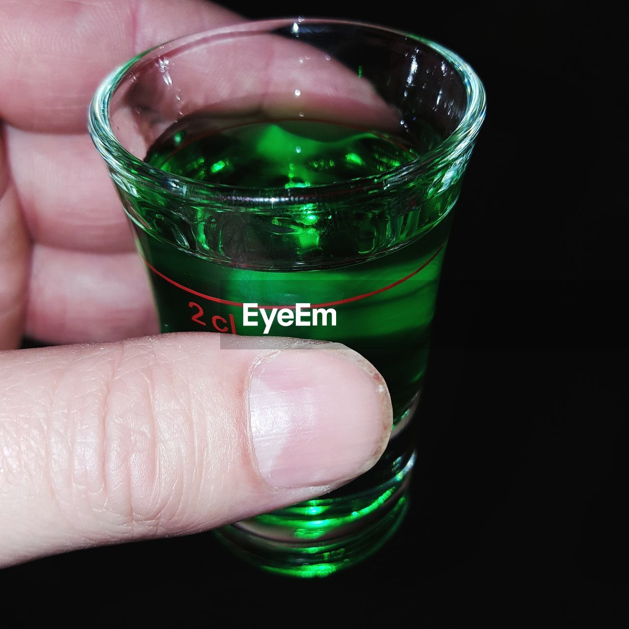 human hand, human body part, real people, holding, one person, human finger, drink, refreshment, food and drink, green color, drinking glass, alcohol, indoors, close-up, shot glass, nail polish, freshness, day, people