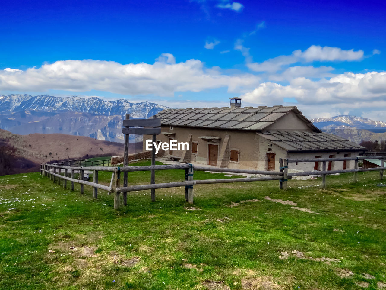 mountain, architecture, cloud - sky, sky, grass, built structure, building exterior, landscape, field, building, nature, land, environment, scenics - nature, day, house, no people, beauty in nature, mountain range, plant, outdoors