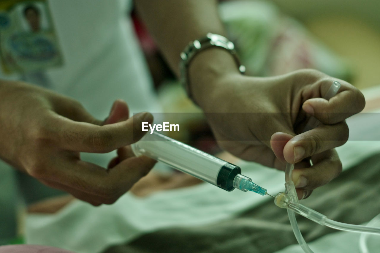 Midsection of nurse injecting syringe at hospital