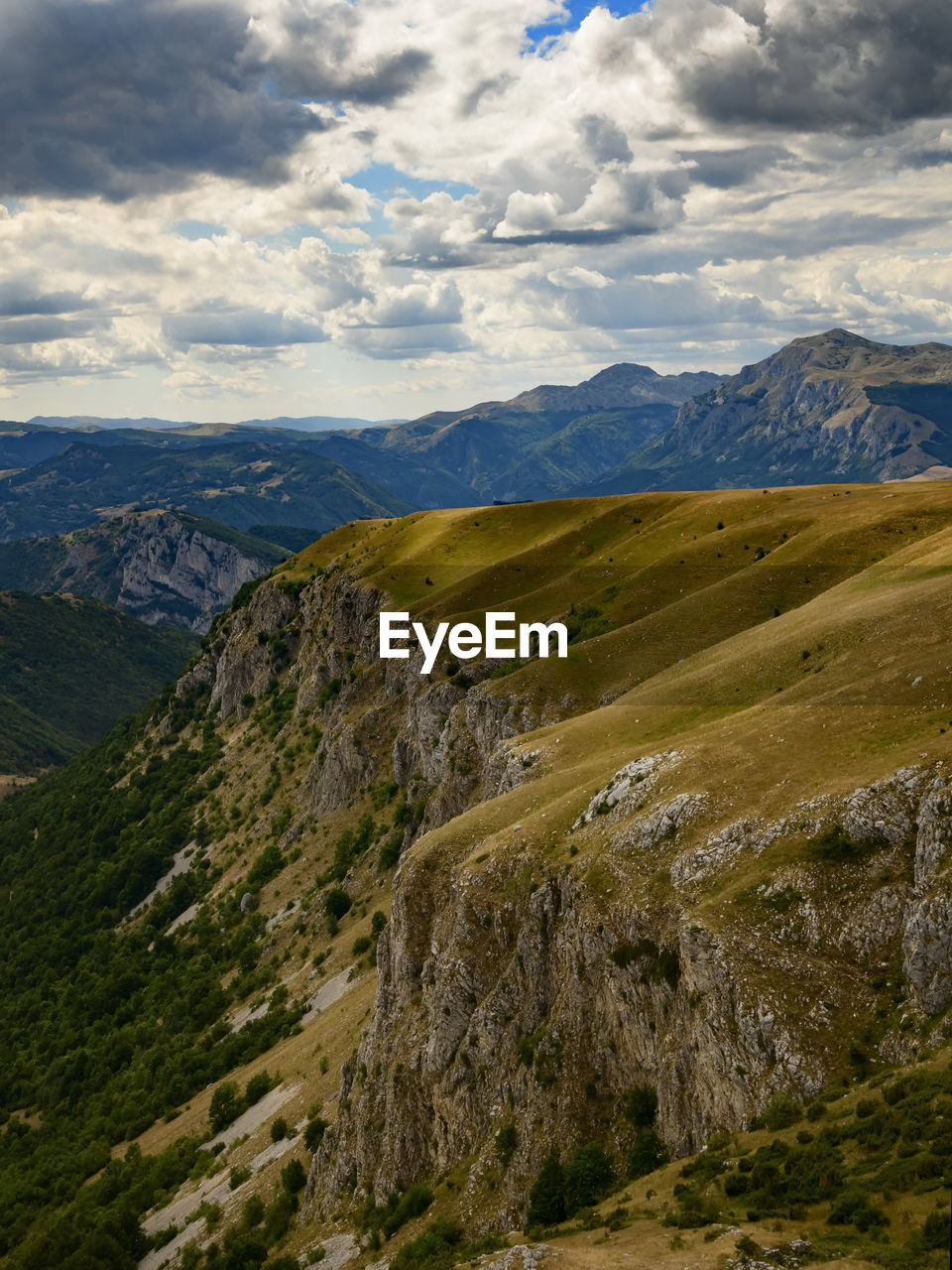 SCENIC VIEW OF VALLEY AND MOUNTAIN AGAINST SKY
