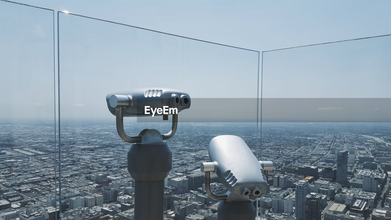 Coin-Operated Binoculars By Glass Against Cityscape