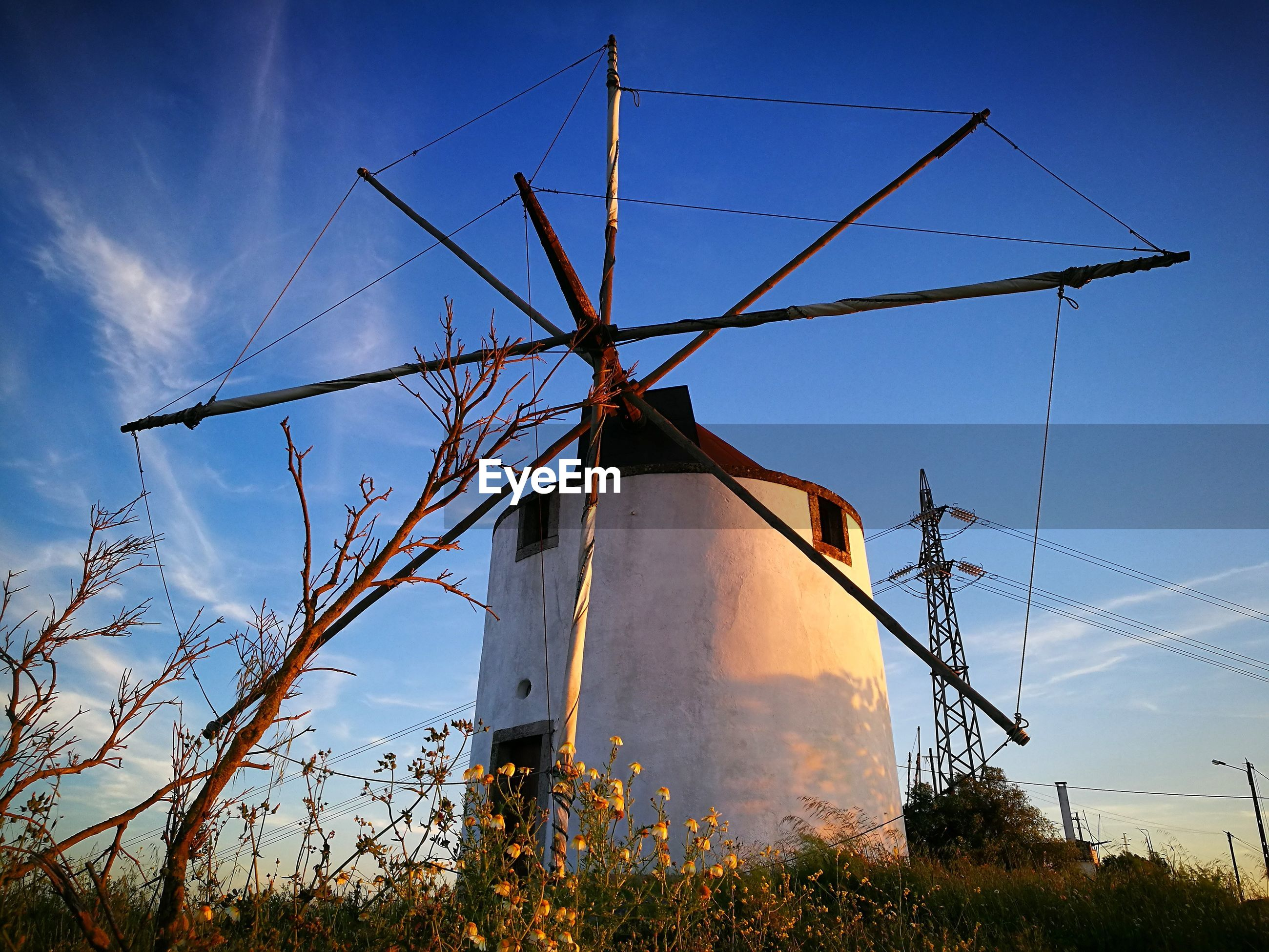 LOW ANGLE VIEW OF WINDMILL ON FIELD AGAINST BLUE SKY