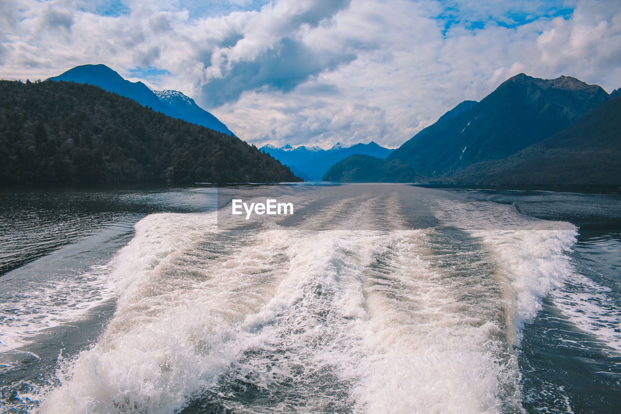 water, beauty in nature, cloud - sky, mountain, scenics - nature, sky, motion, sea, waterfront, wake - water, nature, sport, mountain range, aquatic sport, surfing, day, wake, idyllic, outdoors, flowing water, power in nature, flowing