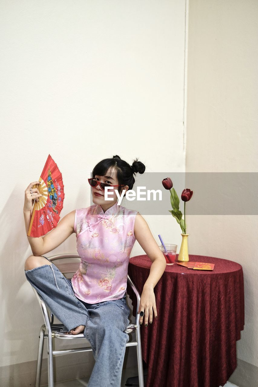 Portrait of woman in pink cheongsam top and jeans holding a fan
