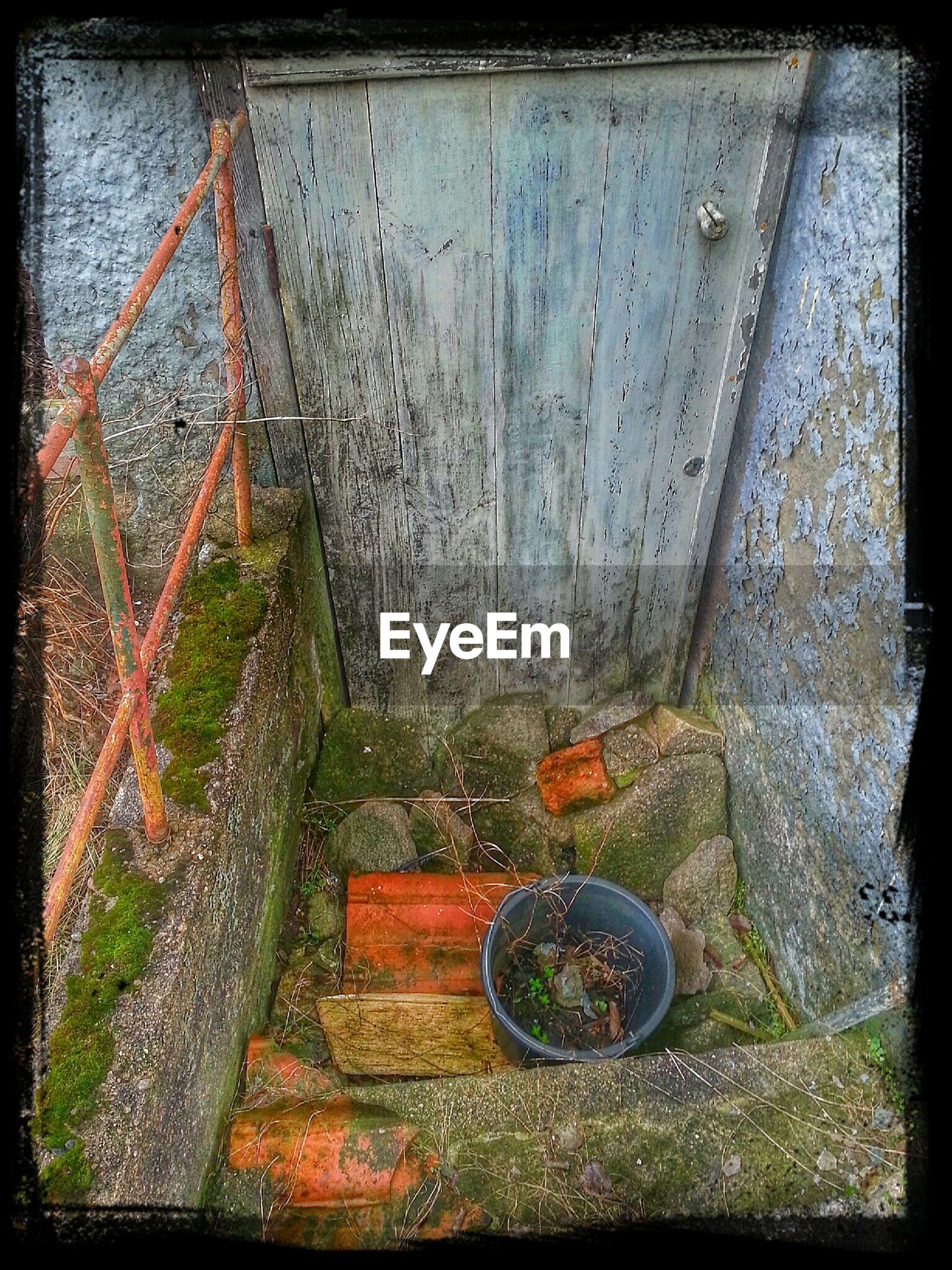 Bucket by door of old building
