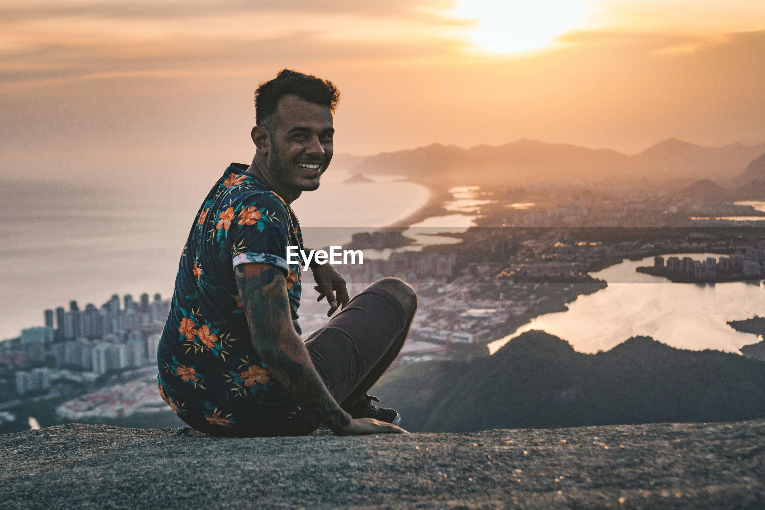 Portrait of man sitting on rock above cityscape