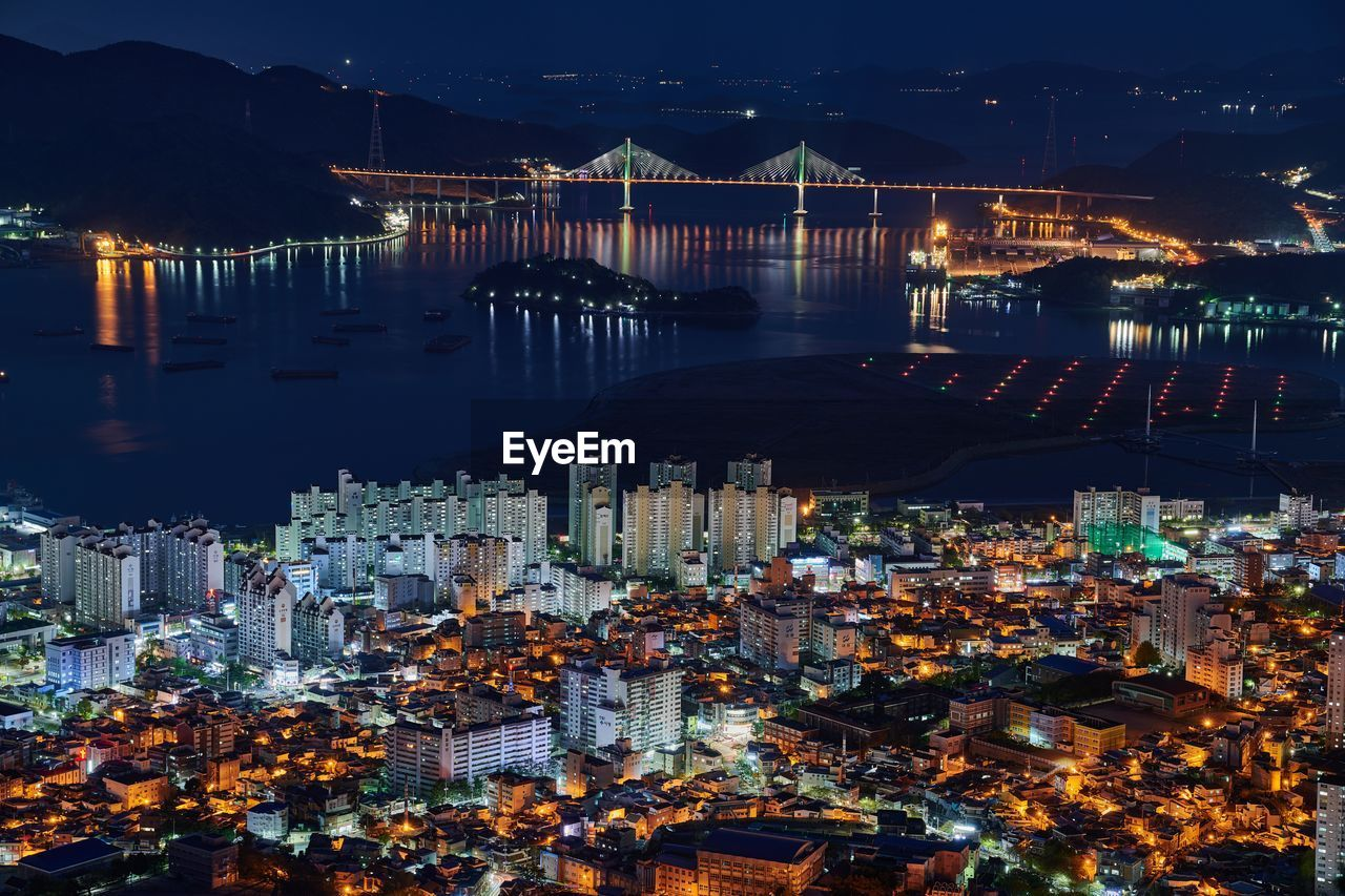 High angle view of illuminated city by buildings at night