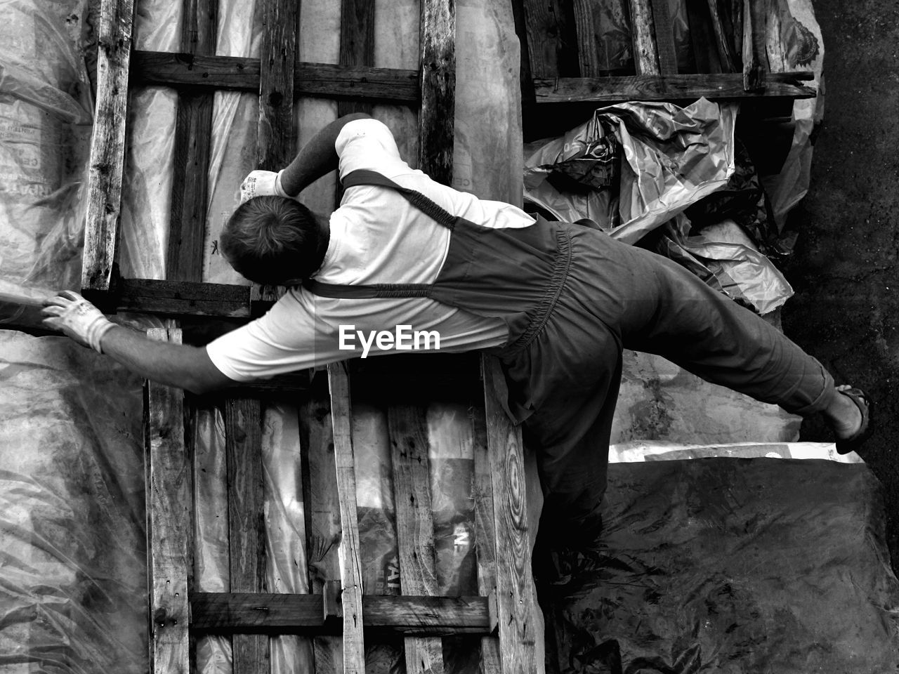 Directly Above Shot Of Man Arranging Wooden Palettes On Tarpaulin