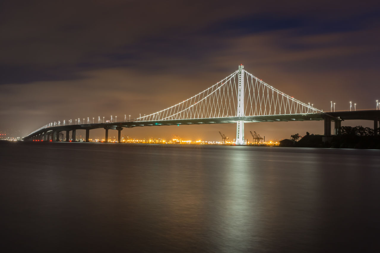 built structure, bridge, bridge - man made structure, architecture, sky, transportation, connection, water, cloud - sky, engineering, suspension bridge, nature, travel destinations, river, night, illuminated, reflection, waterfront, outdoors, bay