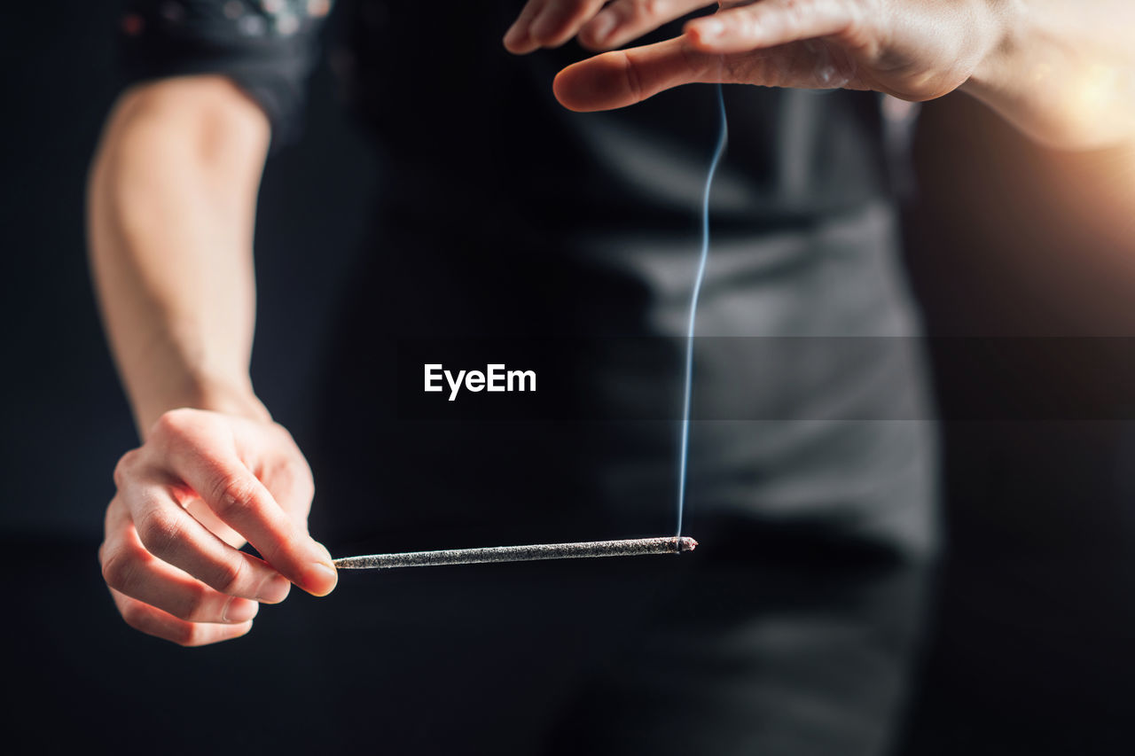 Hands holding a burning incense stick, black background