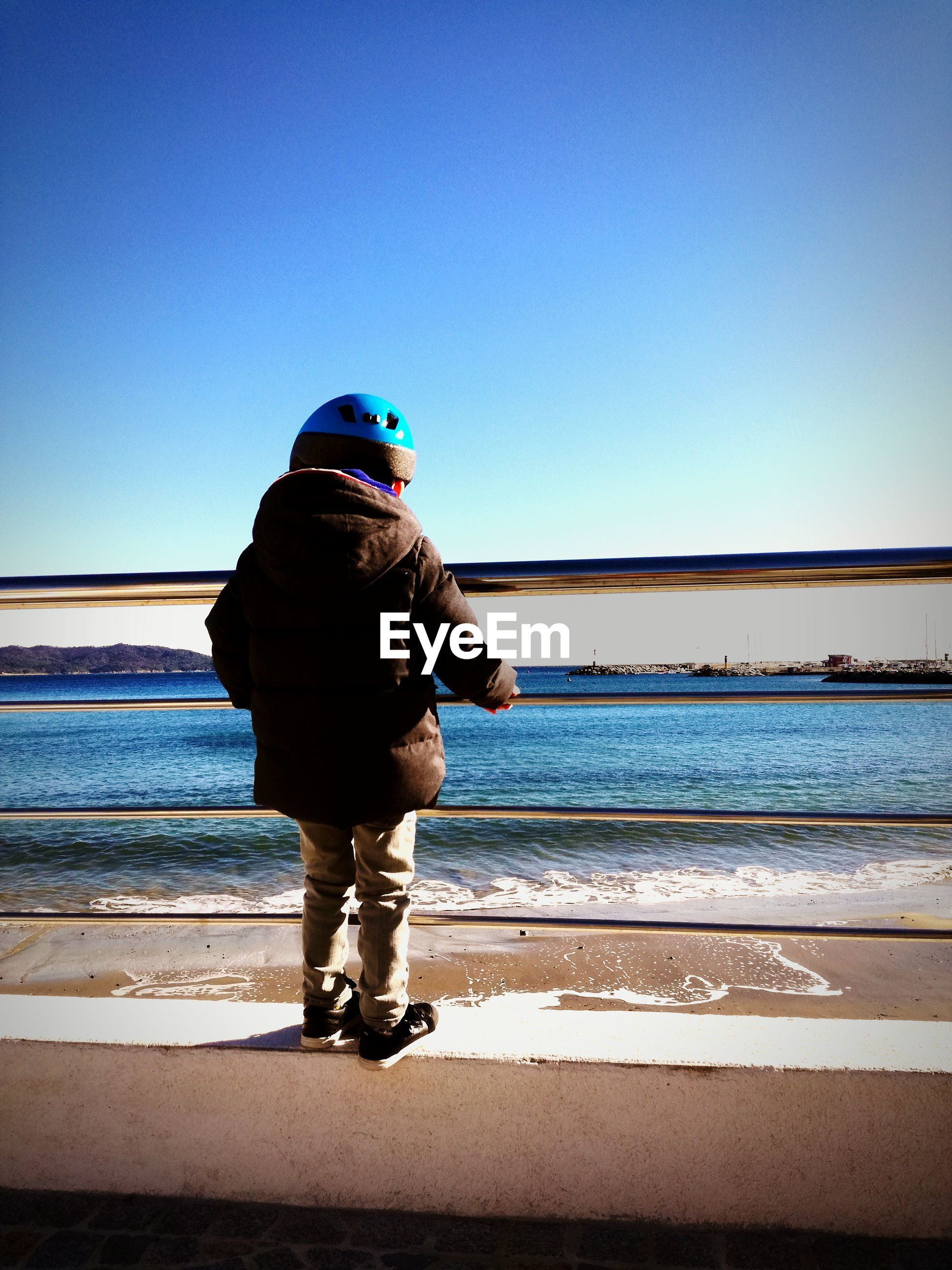 Rear view of boy standing on railing
