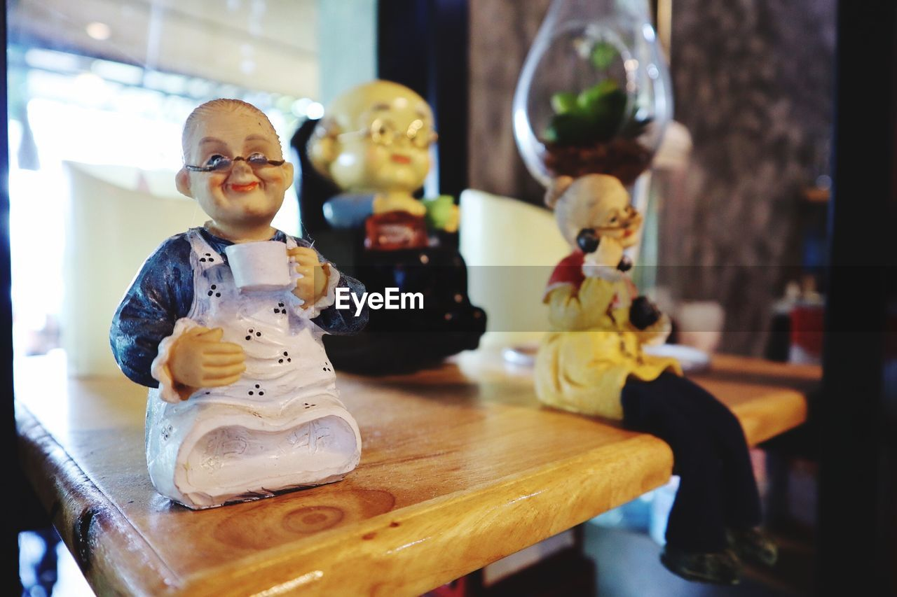 representation, human representation, childhood, table, indoors, toy, still life, male likeness, art and craft, focus on foreground, creativity, figurine, female likeness, close-up, child, day, stuffed toy, home interior, innocence