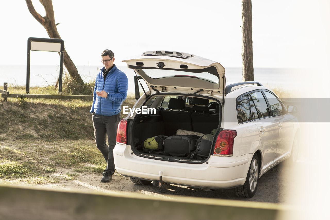 FULL LENGTH OF MAN STANDING ON CAR