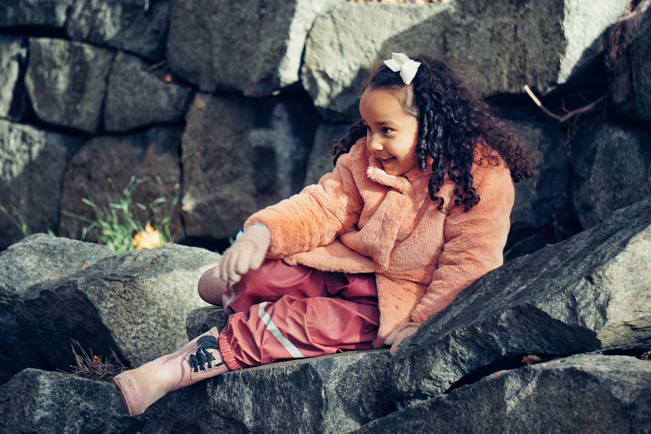 Full length of girl sitting on rocks