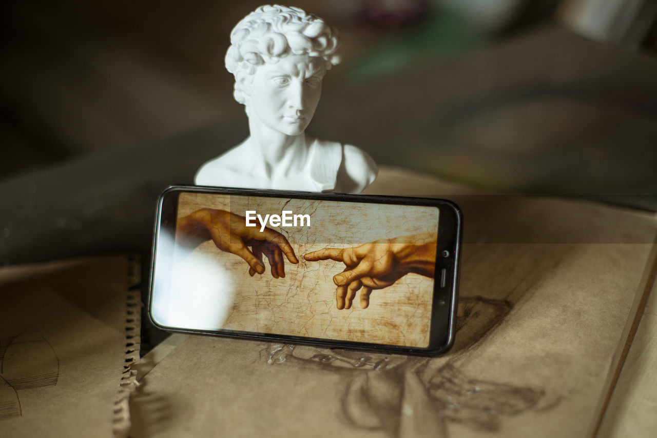 human representation, representation, communication, wireless technology, smart phone, portable information device, male likeness, technology, art and craft, no people, indoors, connection, table, photography themes, creativity, screen, selective focus, mobile phone, close-up, female likeness